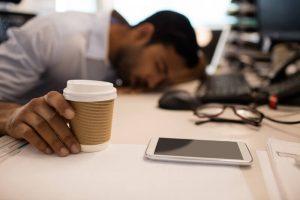 man sleeping at desk | Constellation Nutrition